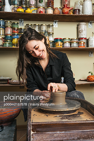 Smiling woman working on workpiece in pottery - p300m2167578 by Vasily Pindyurin