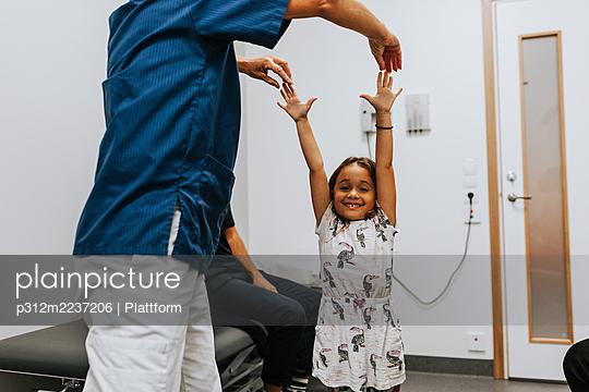 Doctor examining girl in office - p312m2237206 by Plattform