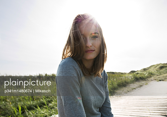Young woman on planked footpath in the dunes - p341m1480674 by Mikesch