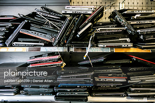 Pile of old, discarded laptops on shelf