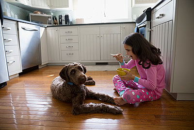 Dog next to girl eating cereal kitchen floor - p1192m1078224f by Hero Images
