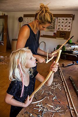 Mother and daughter in workshop working on Stone-Age spear-thrower - p300m1166143 by Tom Chance