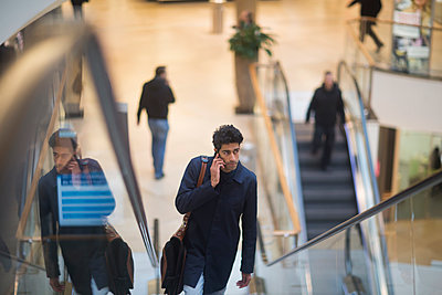 Man on the phone standing on escalator in a shopping mall - p300m1562317 by Sigrid Gombert