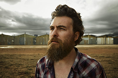 Serious man with full beard in abandoned landscape - p300m965404f by Karsten Koch
