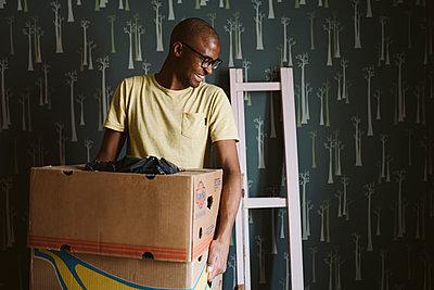 Smiling man carrying cardboard boxes - p312m2146252 by Stina Gränfors