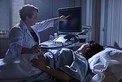 Cropped view of sonographer giving pregnant patient ultrasound scan - p429m1514093 by Philippe Roy