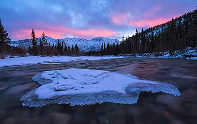 Sunrise over the mountains near Whitehorse with the Wheaton River flowing towards them and clouds reflected into the river; Whitehorse, Yukon, Canada - p442m2074085 by Robert Postma