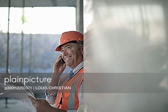 Smiling male architect talking on smart phone at construction site - p300m2250371 by LOUIS CHRISTIAN
