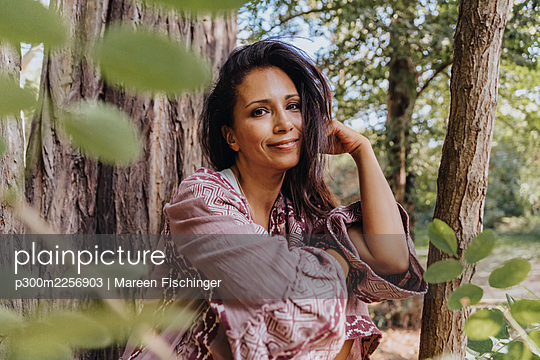Mature woman with hand in hair smiling while sitting under tree - p300m2256903 by Mareen Fischinger