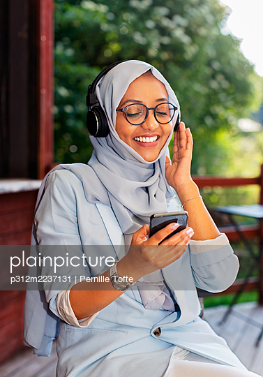 Smiling woman listening music via headphones - p312m2237131 by Pernille Tofte