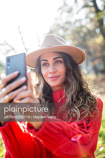 Junge Frau im roten Pullover macht ein Selfie - p975m2222119 von Hayden Verry