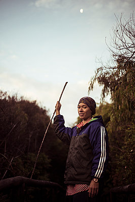 androgynous asian stands with walking stick in beach scrub under moon - p1166m2136704 by Cavan Images