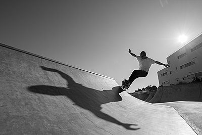 shadow of Skateboarder doing trick - p1201m1050381 by Paul Abbitt