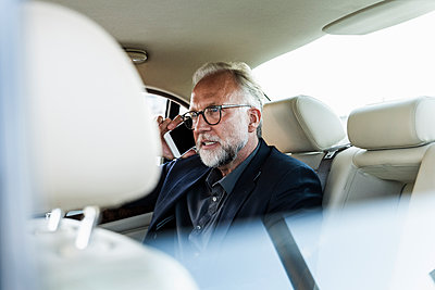 Mature businessman sitting on backseat in car, talking on the phone - p300m2023572 von Uwe Umstätter