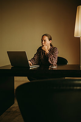 Thoughtful woman working on laptop while sitting in office - p300m2220638 by David Molina Grande
