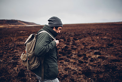 Side view of hiker carrying backpack while walking on barren landscape, Blagoveschensk, Amur, Russia - p301m1482482 by Vasily Pindyurin