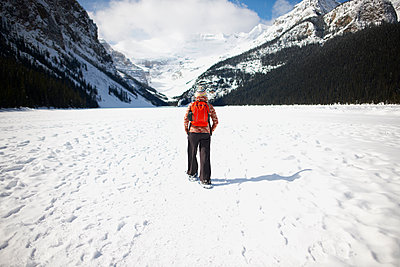 Hiker wearing snowshoes hiking on snow covered landscape, Lake Louise, Canada - p429m1417606 by Peter Muller