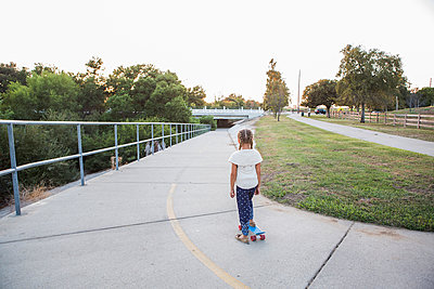 Mixed race girl riding skateboard in park - p555m1411706 by Sam Diephuis