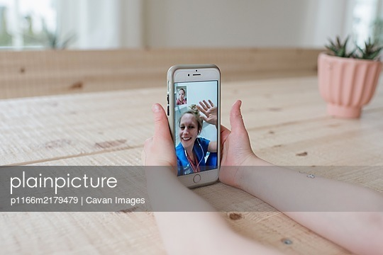 girl having a video call with a nurse at a hospital waving - p1166m2179479 by Cavan Images