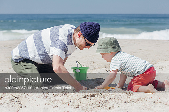 Smiling man digging sand with son at beach during sunny day - p300m2287169 by Ashley Corbin-Teich