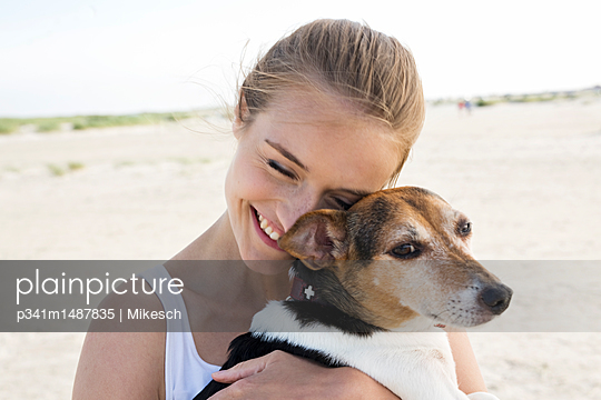 Young woman on beach playing with dog - p341m1487835 by Mikesch
