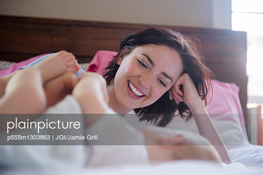 Caucasian mother and baby son laying on bed - p555m1303863 by JGI/Jamie Grill
