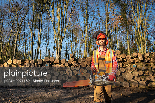 Timber worker with chainsaw and cut logs in sustainable forest - p924m2271182 by Monty Rakusen