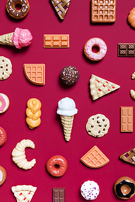 Directly above shot of various dessert toys on red background - p1094m1467617 by Patrick Strattner
