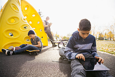 Tween boys using digital tablets and cell phone in sunny autumn park - p1192m1194095 by Hero Images