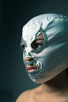 Young black woman with bare shoulders, wearing a Mexican wrestlers mask. - p1433m1589015 by Wolf Kettler
