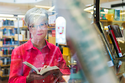 Portrait of senior woman behind glass pane in a city library - p300m2041854 by Frank Röder