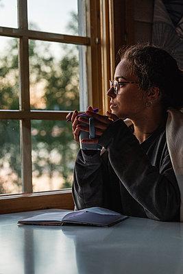 Finland, Lapland, young woman sitting at the window holding a mug - p300m2060850 by Kike Arnaiz