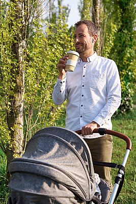 Mid adult man drinking coffee while standing with baby stroller on sunny day - p300m2282850 by Veam