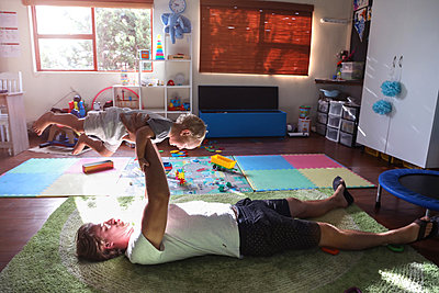 Father lying on floor, lifting baby boy in air - p924m2075138 by Bean Creative