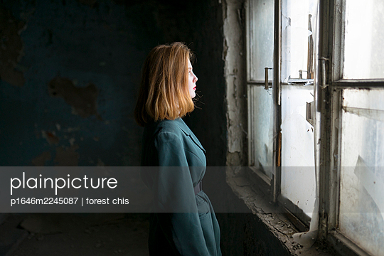 Teenage girl in the staircase looking out of window - p1646m2245087 by Slava Chistyakov