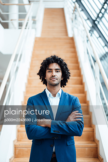 Confident handsome young male entrepreneur standing with arms crossed against staircase at office - p300m2243690 by Joseffson