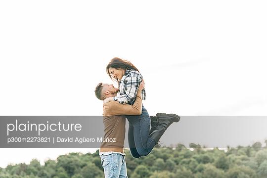 Cheerful boyfriend lifting up girlfriend - p300m2273821 by David Agüero Muñoz