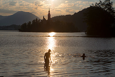 Two boys swimming in Lake Bled at sunset, Bled, Upper Carniola, Slovenia - p343m1576712 by Menno Boermans