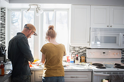 Mid adult couple preparing food in kitchen - p924m836534f by Hugh Whitaker