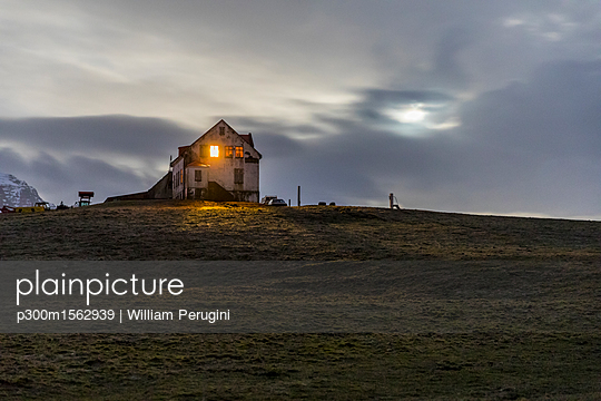 Iceland, Hofn, Illuminated window in a house in the countryside at night - p300m1562939 by William Perugini
