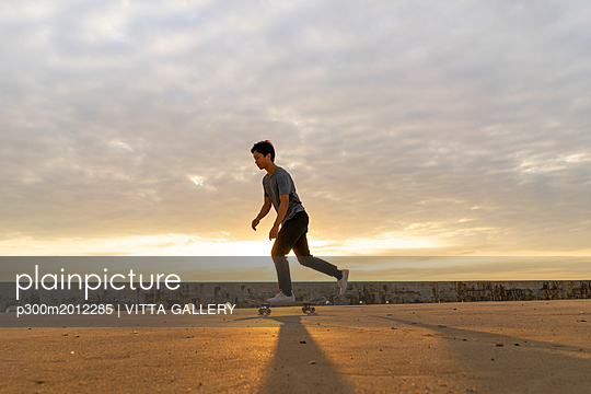 Young Chinese man skateboarding at sunsrise near the beach - p300m2012285 von VITTA GALLERY