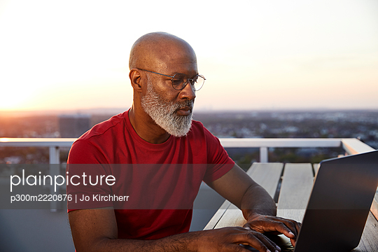 Confident mature bearded man using laptop while sitting on building terrace in city during sunset - p300m2220876 by Jo Kirchherr