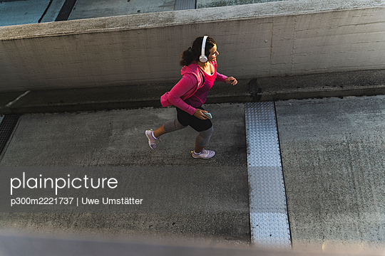 Young woman listening music while jogging on terrace at sunset - p300m2221737 by Uwe Umstätter
