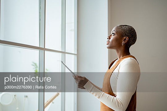 Contemplating woman holding digital tablet while standing in front of window at home - p300m2276390 by Rafa Cortés