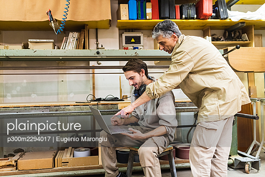 Male carpenters discussing over laptop at workshop - p300m2294017 by Eugenio Marongiu