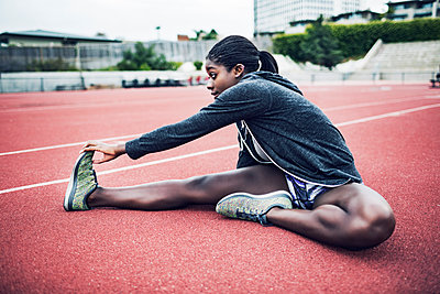 Determined female athlete touching toes while exercising on running tacks - p1166m1086176f by John Trice