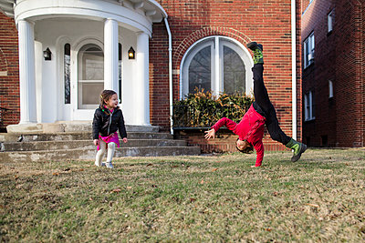Sister looking at brother practicing cartwheel on lawn against house - p1166m1576647 by Cavan Images