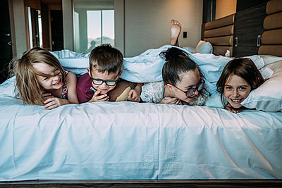 kids laying on bed in hotel room on vacation - p1166m2157235 by Cavan Images