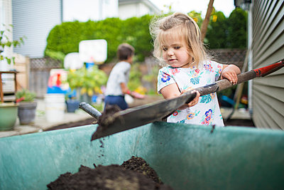 Cute girl shoveling dirt into wheelbarrow in backyard. - p1166m2208468 by Cavan Images