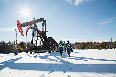 Workers walking toward drilling rigs in snow - p1192m1128006f by Hero Images